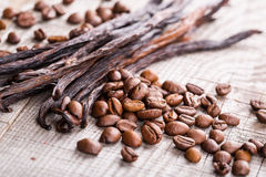 Vanilla pods and coffee beans. On wooden background Stock Images