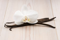 Vanilla pods and flower. On the wooden background Stock Photo