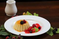 Vanilla pudding with berries and cream. On a white plate close-up stock image