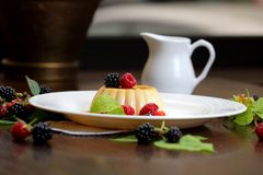 Vanilla pudding with berries and cream. On a white plate close-up stock photos