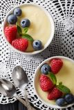 Vanilla pudding decorated with raspberries and blueberries close. Up on the table. Vertical top view from above Royalty Free Stock Photos
