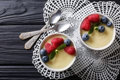 Vanilla pudding with fresh berries and mint closeup. Horizontal. Vanilla pudding with fresh berries and mint closeup on the table. Horizontal top view from above Royalty Free Stock Photos