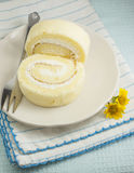 The vanilla roll cake. On the blue stipes clothes,yellow small flower on blue pale background Royalty Free Stock Image