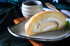 Vanilla Roll Cake on White Dish. With hot tea on background royalty free stock images