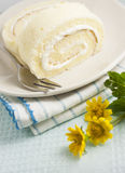 Vanilla roll cakes. The vanilla roll cake on the blue stipes clothes,yellow small flower on blue pale background Royalty Free Stock Images