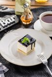 Vanilla souffle with dark chocolate glaze and cup of tea on black table. Side view stock photo