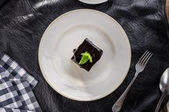 Vanilla souffle with dark chocolate glaze and cup of tea on black table. Top view stock photo