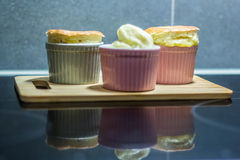 Vanilla souffle with vanilla ice cream. Served on a wooden board and reflected on the stove royalty free stock photography