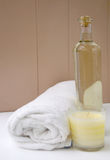 Vanilla Spa. Vanilla scented candle and massage oil and white towel in beige and calming colours to show relaxing spa Royalty Free Stock Photography