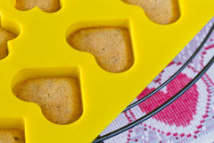 Vanilla  sponge cake hearts in yellow silicone mold. On cooling ruck Royalty Free Stock Photography