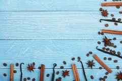 Vanilla sticks, cinnamon, coffee beans and star anise on blue wooden background with copy space for your text. Top view. Stock Photography