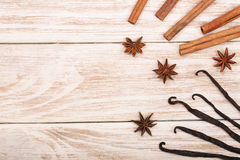 Vanilla sticks, cinnamon, coffee beans and star anise on white wooden background with copy space for your text. Top view Royalty Free Stock Photos