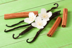 Vanilla sticks and cinnamon with flower and leaf on a green wooden background Royalty Free Stock Photo