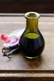 Vanille-Extrakt in einer Flasche und in einer Vanille lizenzfreie stockfotos