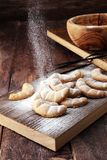 Vanille Kipferl cookies for christmas on brown wooden table with. Sugar Stock Photos