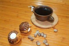 Vanille- und Schokoladenmuffins mit einem Tasse Kaffee, Nüssen und Zimt lizenzfreie stockbilder