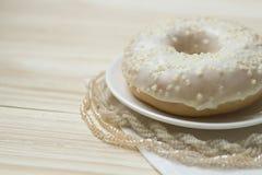 Vanilledonut und -perlen auf einem hölzernen backgroung Stockbild