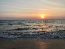 Vanillehimmel und Ozeanstrand wenn Sonnenuntergang stockfotografie