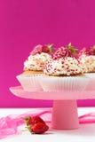 Vanillekleine kuchen verzierten Erdbeeren auf einem rosa backgground Lizenzfreie Stockbilder