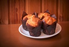 Vanillemuffins in den Papierhaltern des kleinen Kuchens auf Holztisch Stockbilder