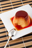 Vanillesahne und Karamellnachtisch mit Löffel auf weißem Teller stockfotos