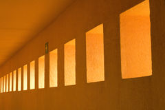 Vanishing Orange Portico. Abstract photo of geometric shapes showing a row of rectangular wall cutouts leading to a vanishing point along a portico wall stock photo