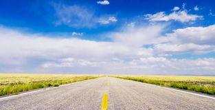 Vanishing point. A straight road in Wyoming disappearing in the distance. A straight Wyoming road disappearing in the distance. Under a bright blue sky and Stock Image
