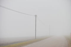 Vanishing road in fog Royalty Free Stock Photos