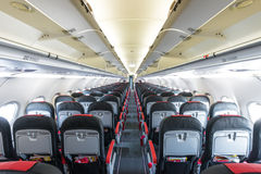Vanishing row of black and red seats in airplane. stock image