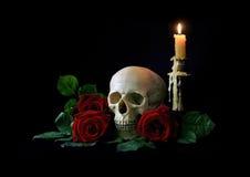 vanitas Cranio umano con le rose rosse sopra bagkground nero Fotografia Stock