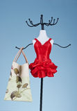 Vanity. Dummy hanger in red dress holding a shopping bag Royalty Free Stock Photo