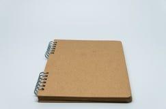 Vanlig anteckningsbok för brunt med vit bakgrund och den selektiva fokusen Royaltyfri Foto