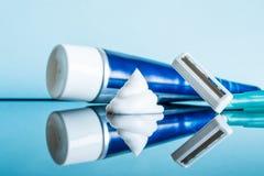 Vanlig disponibel rakkniv och raka kräm i ett modernt badrum på en reflekterande yttersida för exponeringsglas mot en blå bakgrun fotografering för bildbyråer