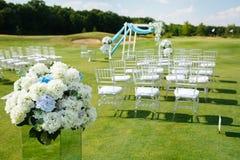 Vanlig hortensiablommaordningar för att gifta sig Suddiga rader av vita stolar på grön gräsmatta för en bröllopceremoni Royaltyfria Foton