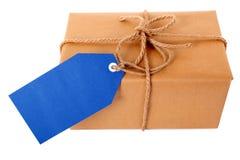 Vanlig packe eller jordlott för brunt papper, blå gåvaetikett eller etikett som isoleras på vit Royaltyfri Fotografi