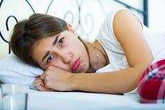 Vanlig tonårs- flicka med ledsen blick i säng Royaltyfri Bild