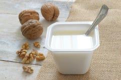 Vanlig yoghurt på en säcktorkduk med några muttrar Royaltyfria Bilder