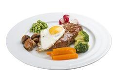 Vanliga frukostbiff, ägg och grönsaker arkivbild