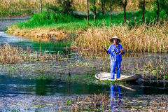 VANLONG NATURAL RESORT, NINHBINH, VIETNAM - NOVEMBER 23, 2014 - An unidentified man fishing on the lagoon. Stock Photos