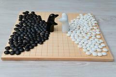 Vanno i pezzi del gioco e due figure in bianco e nero Fotografia Stock Libera da Diritti