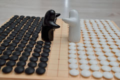 Vanno i pezzi del gioco e due figure in bianco e nero Fotografie Stock