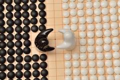 Vanno i pezzi del gioco e due figure in bianco e nero Fotografie Stock Libere da Diritti