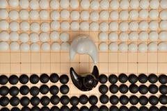 Vanno i pezzi del gioco e due figure in bianco e nero Fotografia Stock