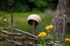 Vantage ceramic clay pot hanging on willow fence surrounded by y stock photos
