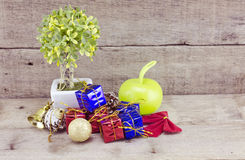 Vantage look Christmas decorations with red ball,green ball,red ribbon,bell,small tree on white pot, and artificial flower. aged a Stock Images