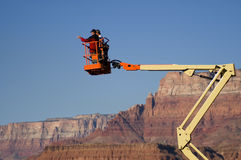Vantage Point. Men in bucket lift look out over the Colorado River at Lee's Ferry in Marble Canyon while filming a documentary movie Stock Images