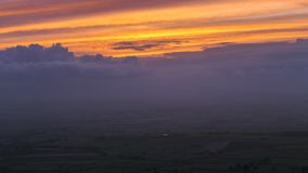 Hazy Autumnal Sunset over Scenic Hills in UK. Vantage view over hazy fields of British countryside with orange setting sun over scenic hills. Time-lapse stock video footage
