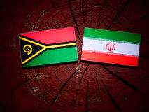 Vanuatu flag with Iranian flag on a tree stump isolated. Vanuatu flag with Iranian flag on a tree stump Stock Photo
