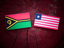 Vanuatu flag with Liberian flag on a tree stump isolated. Vanuatu flag with Liberian flag on a tree stump Stock Image