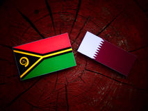 Vanuatu flag with Qatari flag on a tree stump isolated. Vanuatu flag with Qatari flag on a tree stump Stock Photography
